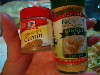 Hand holding ground cumin and ginger containers