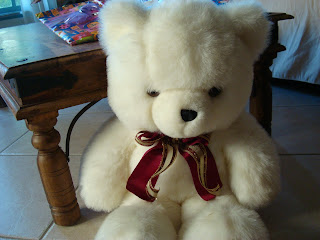 Stuffed white bear with bow around neck