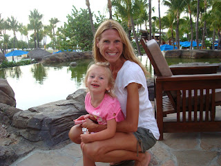 Woman and young girl hugging at hotel in front of water feature