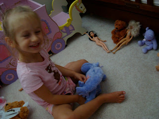 Young girl sitting on floor playing with barbies