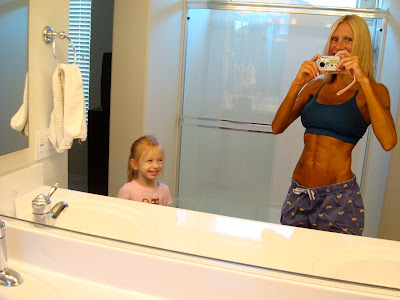 Woman in mirror showing off spray tan with young child looking on