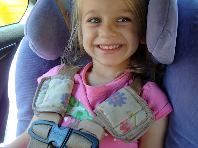 Close up of young girl buckled into car seat