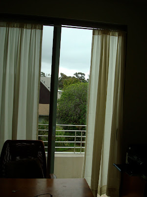 Curtains on window with open door to balcony