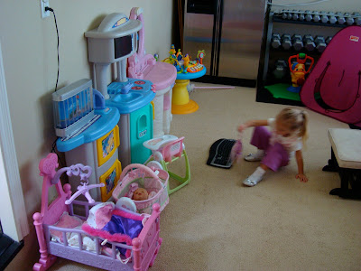 Toy room with multiple toy set ups and young girl playing