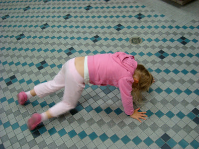 Young girl on floor on knees trying to do yoga pose
