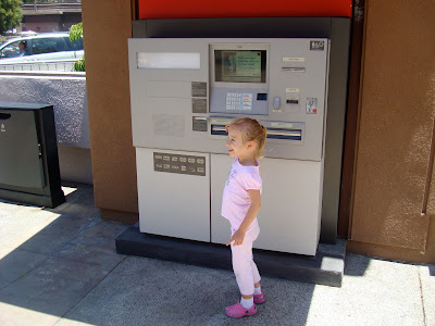 Young girl standing by ATM machine