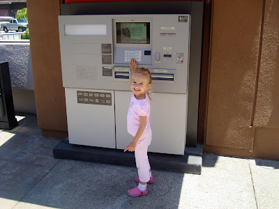 Young girl at ATM machine smiling