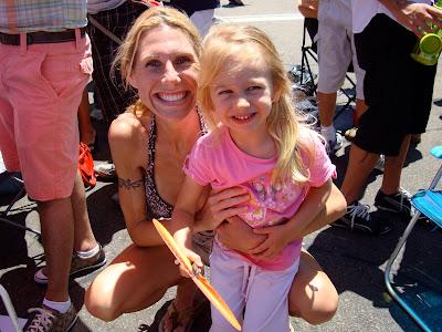 Woman squatting next to young girl at Gay Pride Parade