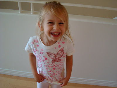 Young girl tugging on shirt and giving a huge smile