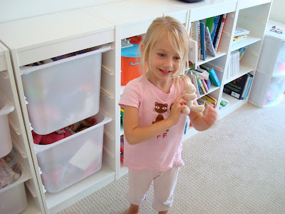 Young girl standing in room holding a toy