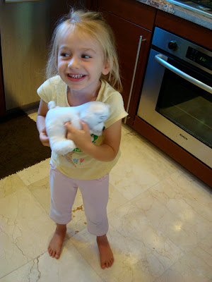 Young girl in kitchen holding toy