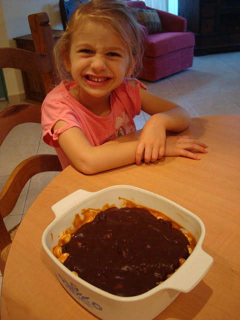 Little girl smiling with GF Peanut Butter Marshmallow Bars with Vegan Chocolate Frosting on table