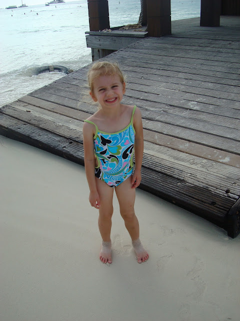 Young girl in bathing suit next to pier