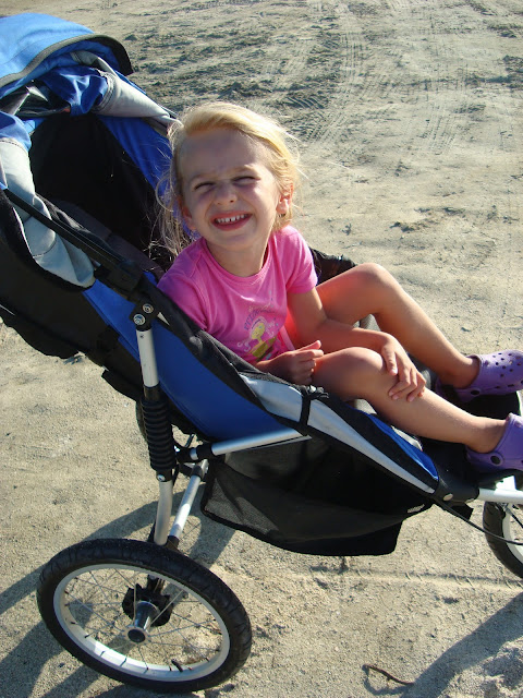 Young girl in stroller leaning over and smiling