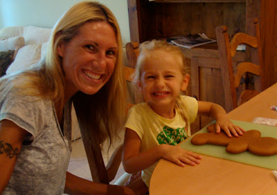 Woman and young girl at table with gingerbread man smiling