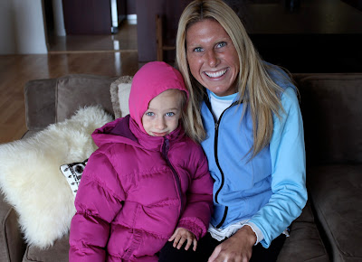 Young girl in puffer jacket sitting on couch with woman in blue vest