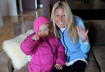 Young girl in jacket and woman in vest on couch waving