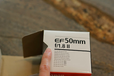 Hand holding empty box for camera lens