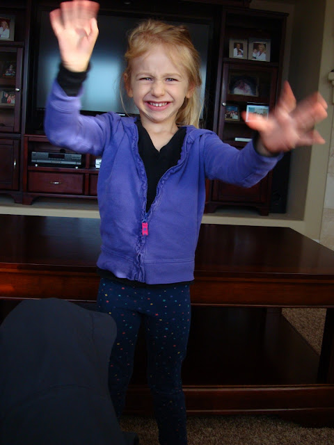 Child making silly face with arms up