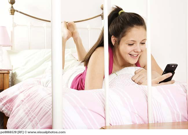 teen texting in bed