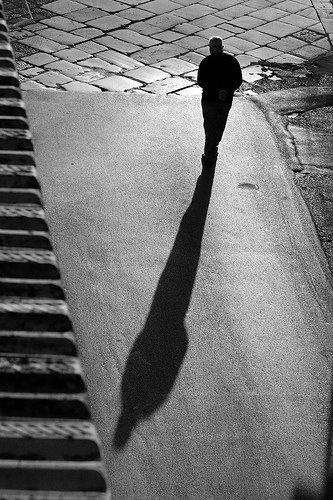 Homem solitário caminhando pela rua.