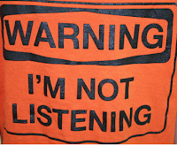 T-shirt that says, WARNING I am not listening 
