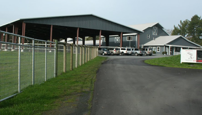 driveway leading up to several large grey farm-style buildings