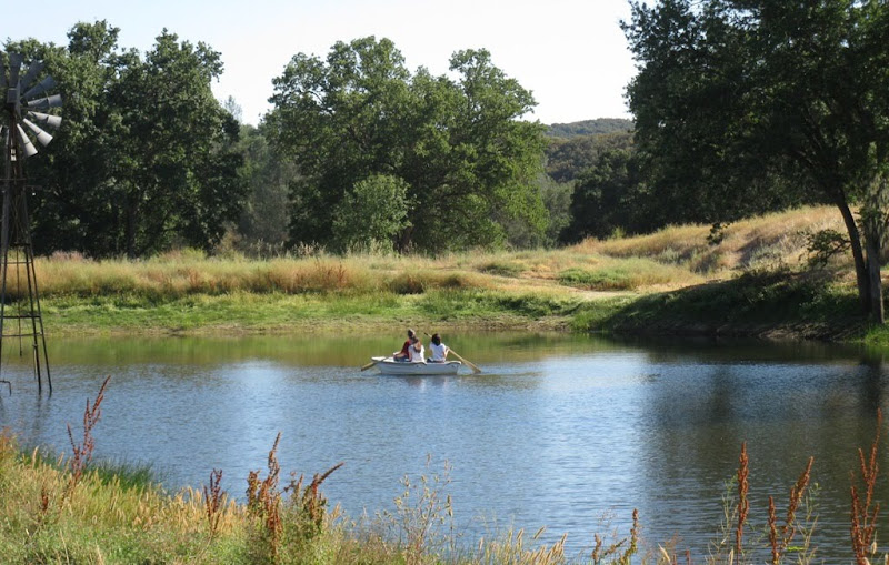 my husband and daughters rowing a little rowboat in middle of the pond