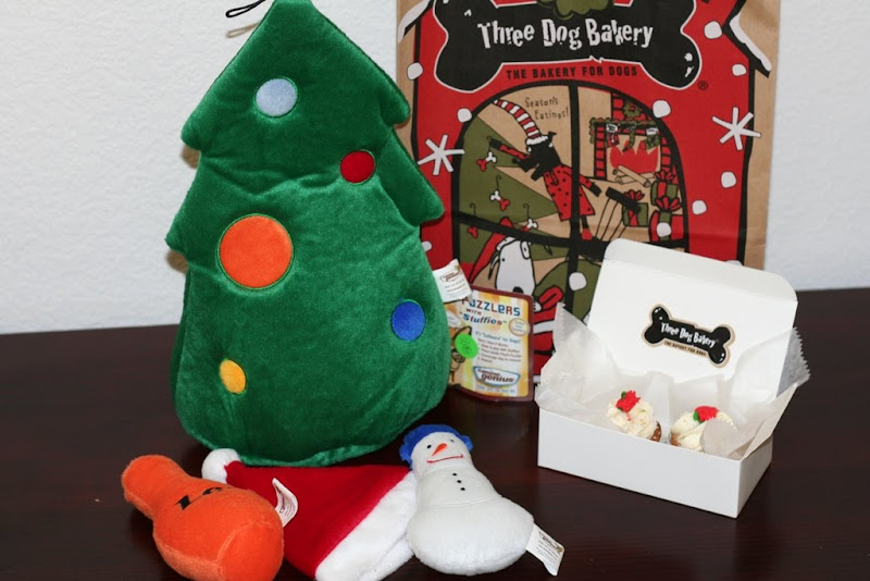 stuffed christmas tree toy with little stuffed toys in front which include a santa hat, an orange thing I have no idea what it is, and a snowman, there's also a little white bakery box with two tiny cupcakes inside, each has a little red flower on top of white frosting