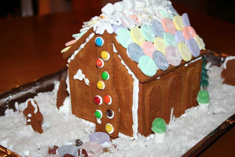 gingerbread house sitting on a bed of shredded coconut, decorated with white icing, M&Ms, necco wafers