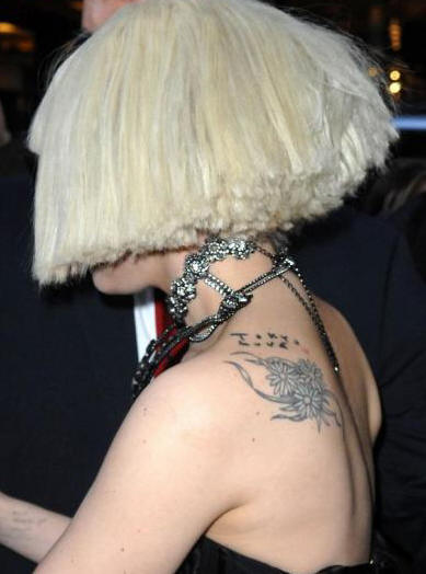 Picture of Lady Gaga's peace sign wrist tattoo and words tattoo on her arm