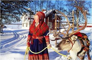 Senhora vestida com roupa tradicional da Lapónia segura Rena