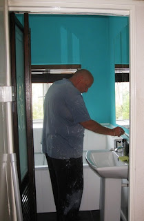 Decorator adding finishing touches to the bathroom paint