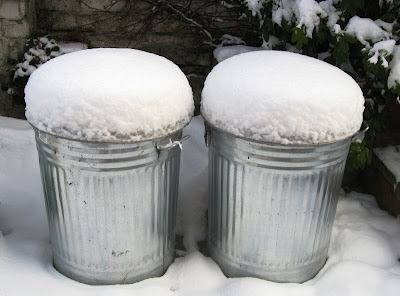 Snow piled on top of two metal bins
