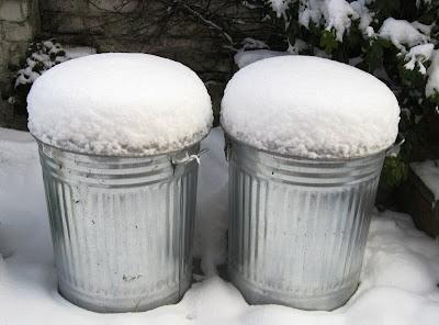 Snow piled on top of two metal bins