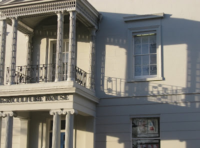Two-storey portico and shadow, with columns and wrought iron