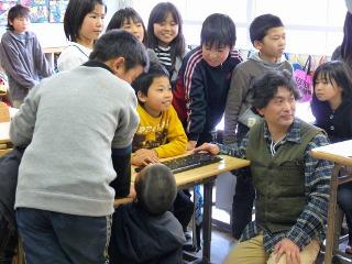 代表の生徒さんを囲んでキーボード操作による点字作成をしている写真
