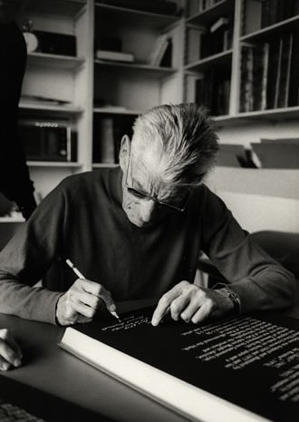Samuel Beckett at his apartment in Paris signing a rare Limited Edition copy of The Lost Ones