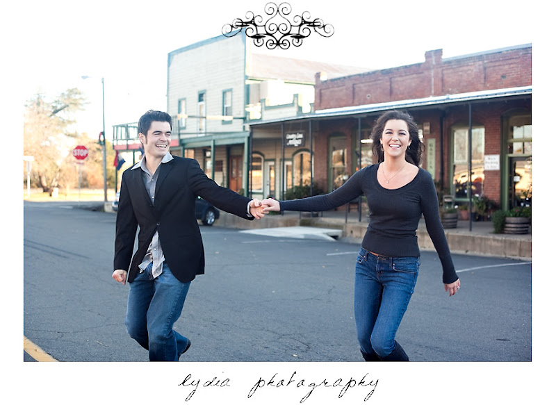 Bride and groom dancing in the middle of the street at lifestyle old town engagement portraits in Cottonwood, California