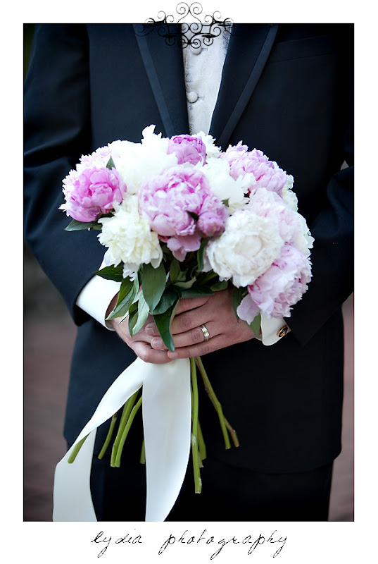 Groom holding the bride's pink and white peony bouquet at an Empire Mine State Park wedding