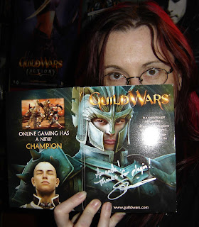 Your blogger - a woman with red hair and glasses - peers over top of a box for the game Guild Wars, which has been autographed in silver pen