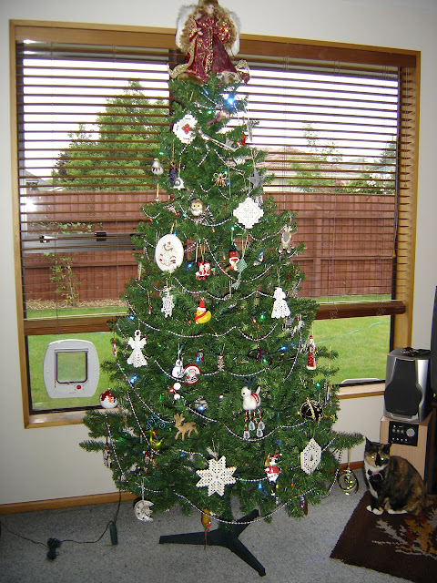 A six foot decorated Christmas tree, with a calico cat sitting beneath.