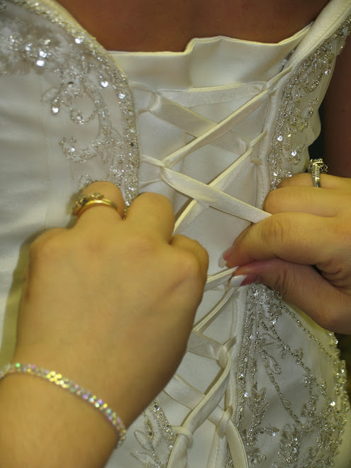 Her sister lacing her dress