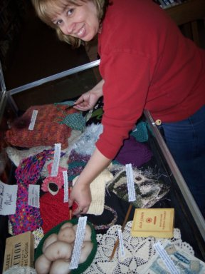 Dee setting up a crochet display at a local library in honor of National Crochet Month, 2008