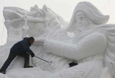 A worker carves a snow sculpture