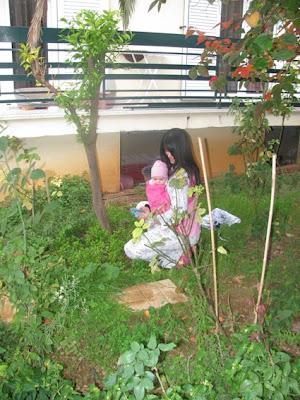 Με το μωρό στο μάρσιπο, η μαμά καθαρίζει τον κήπο της