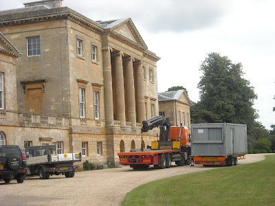 One of three large containers being delivered outside the mansion, to be used as a work site office space