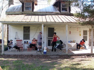 cabin front porch with people standing and sitting around