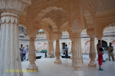Tourists inside one of the halls (between the pillars) in the Amer Fort in Jaipur