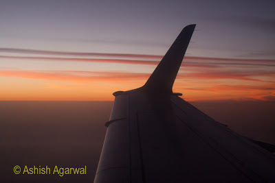The wing of a place in the sky over Aswan, with brilliant colors of sunset